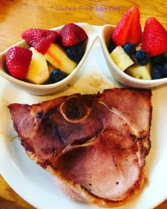 A picture of Cracker Barrel's sugar-cured ham and two bowls of fresh fruit.