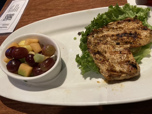 Grilled Chicken on lettuce with bowl of fresh fruit